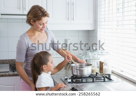 Mother and daughter cooking together at home in kitchen - stock photo