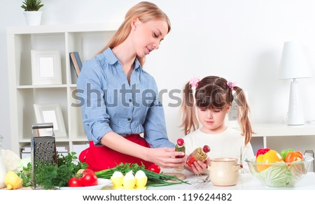 Mother and daughter cooking together, help children to parents - stock photo
