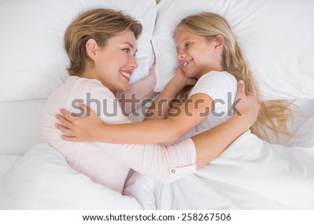 Mother and daughter cuddling in bed at home in the bedroom