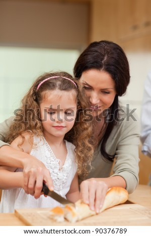Mother and daughter cutting bread into slices together - stock photo