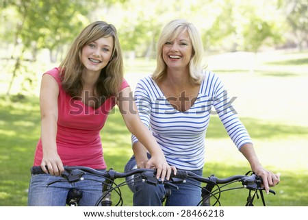 Mother And Daughter Cycling Through A Park - stock photo