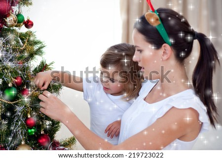 Mother and daughter decorating a Christmas tree against snow - stock photo