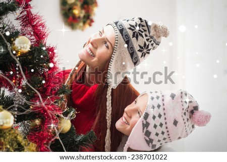 Mother and daughter decorating christmas tree against snow - stock photo