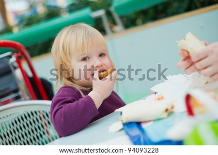 Mother and daughter dinning fast food meal in mall - stock photo