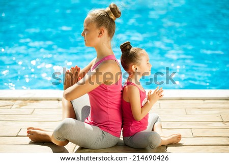 Mother and daughter doing exercise outdoors. Healthy lifestyle. Yoga - stock photo