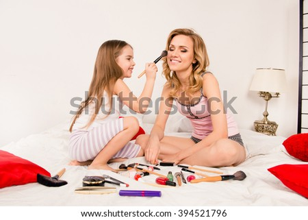 Mother and daughter doing  makeup sitting on the bed in the bedroom - stock photo