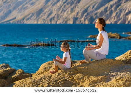 Mother and daughter doing yoga exercise on the beach - stock photo