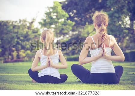 Mother and daughter doing yoga exercises on grass in the park at the day time - stock photo