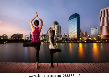 Mother and daughter doing yoga tree pose at city - stock photo