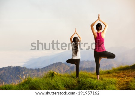 Mother and daughter doing yoga Tree pose at top of mountain