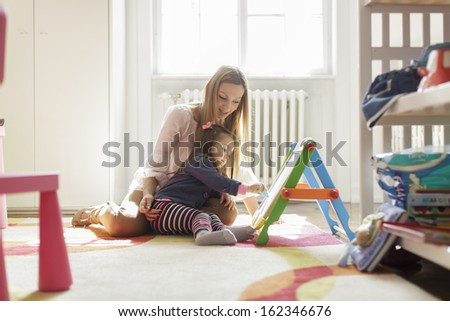 Mother and daughter drawing in the room - stock photo