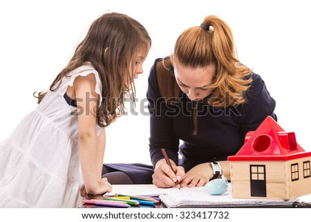 Mother and daughter drawing on papers home  - stock photo
