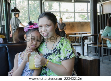 Mother and daughter drinking orange juice in restaurant