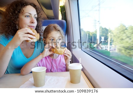 Mother and daughter eat and drink, sitting in armchair at table near window of moving speed train - stock photo