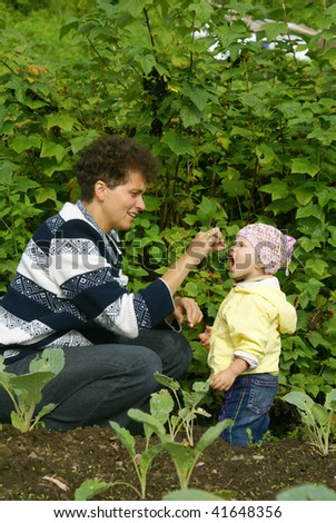 mother and daughter eat berry of the currant in garden
