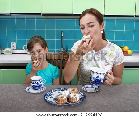 Mother and daughter eat muffins and drink tea in kitchen - stock photo
