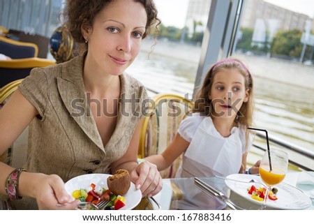 Mother and daughter eating at the floating  restaurant with a river view