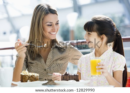 Mother and daughter eating cake and drinking juice in cafe - stock photo