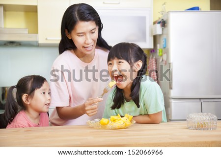 Mother and daughter eating fruits in the kitchen