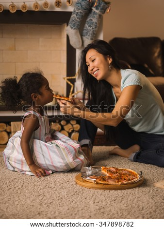 Mother and Daughter eating pizza at home - stock photo