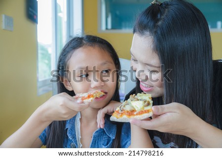 Mother and daughter eating pizza in restaurant.