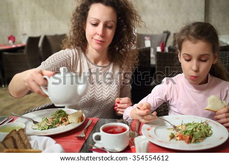Mother and daughter eating salad and drinking tea at a table in a restaurant - stock photo