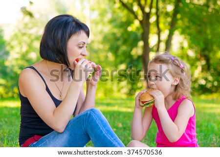Mother and daughter eating sandwiches at a picnic in the park - stock photo