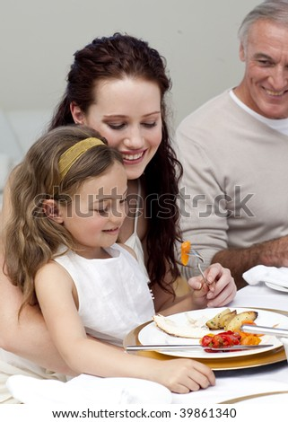 Mother and daughter eating with their family at home