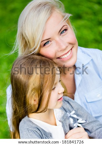 Mother and daughter embrace each other sitting on the grass. Leisure time of happy family - stock photo