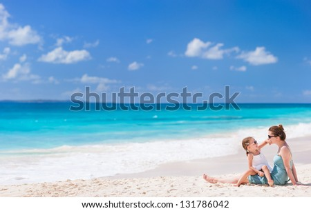 Mother and daughter enjoying beach vacation - stock photo