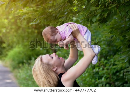 Mother and daughter European appearance on the walk have fun summer in the Park, mom holds daughter high above his head, the sun, summer, Park, summer weather - stock photo