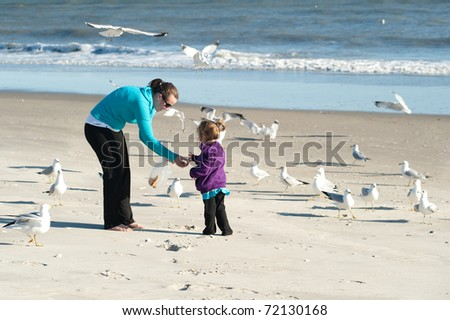mother and daughter feeding birds at the beach - stock photo