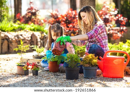 Mother and daughter gardening together.They planting the flowers. - stock photo
