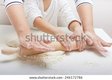 Mother and Daughter Hands Kneading Dough on the table.
