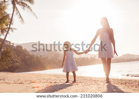 mother and daughter happy in love at sunset - stock photo