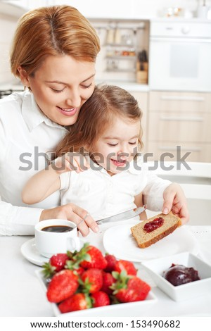 Mother and daughter having breakfast together - stock photo