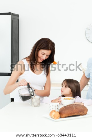 Mother and daughter having breakfast with their family in the kitchen