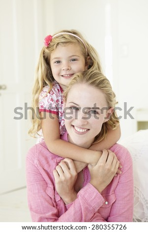 Mother And Daughter Having Cuddle Together At Home - stock photo