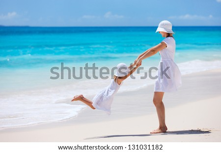 Mother and daughter having fun at tropical beach - stock photo