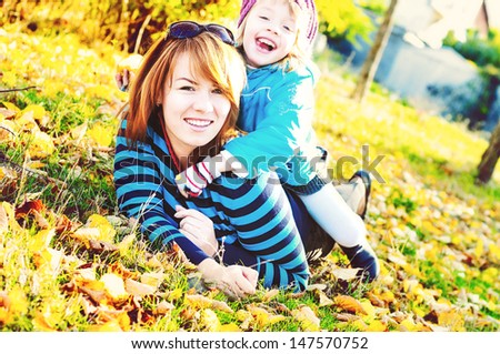 mother and daughter having fun in  fall park - stock photo