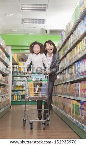 Mother and Daughter Having Fun in Supermarket, Pushing Cart - stock photo