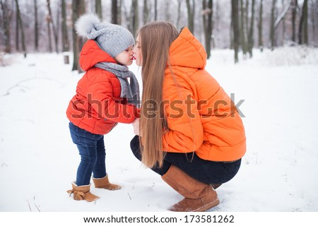 Mother and daughter having fun in the winter forest - stock photo