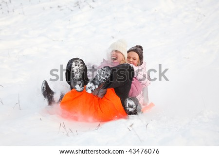 Mother and daughter having fun in winter by sliding down hill