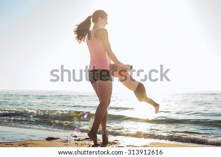 mother and daughter having fun on beach - stock photo