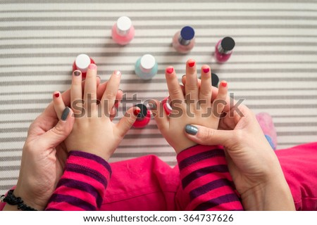 Mother and daughter having fun painting fingernails, family time concept, view from above - stock photo