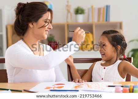 Mother and daughter having fun while painting at home - stock photo
