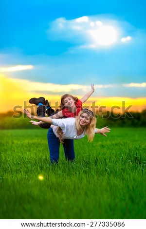 Mother and daughter Having Fun. Young mother with child outside on a summer day - stock photo