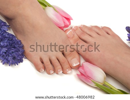 Mother and daughter having spa treatment ( pedicured feet and aromatic flowers) - stock photo