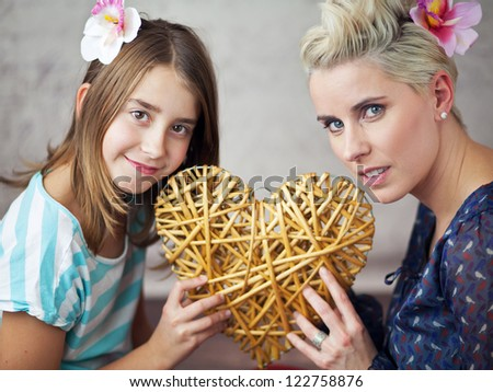 Mother and daughter holding a heart - stock photo