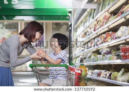 Mother and daughter holding apple, shopping for groceries, Beijing - stock photo